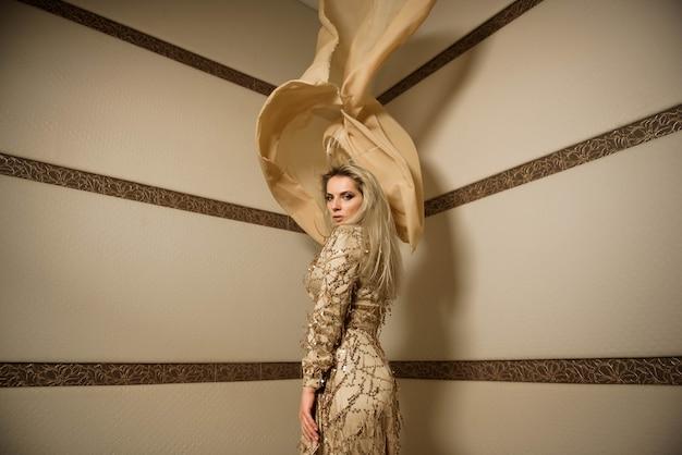 Blond meisje model plus grootte in de hoek van de kamer met een grote gesneden stof