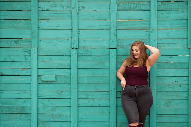 Blond meisje model plus size op de achtergrond van een groene muur.