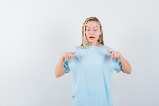 Blond meisje naar beneden met wijsvingers in blauw t-shirt en gefocust op zoek. vooraanzicht.