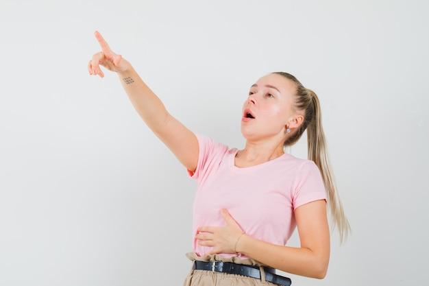 Blond meisje omhoog in t-shirt, broek en op zoek verrast, vooraanzicht.