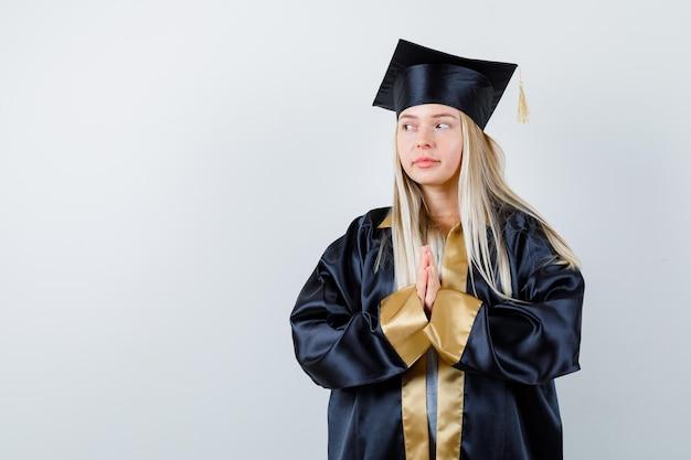 Blond meisje omklemde handen in een biddend gebaar in afstudeerjurk en pet en zag er serieus uit.