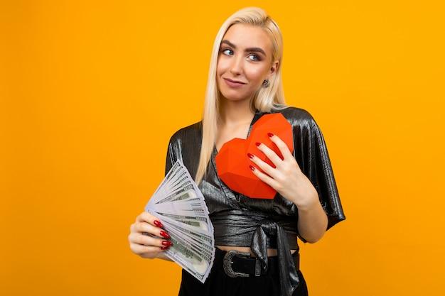Blond meisje ontving een geldgeschenk en heeft een papieren hart in zijn handen