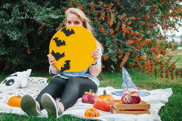 Blond meisje op de deken in het park op het gazon met een spook en pompoenen halloween-symbolen