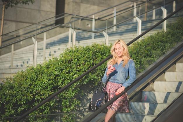 Blond meisje op de roltrap met behulp van een smartphone op zoek naar het scherm glimlachen