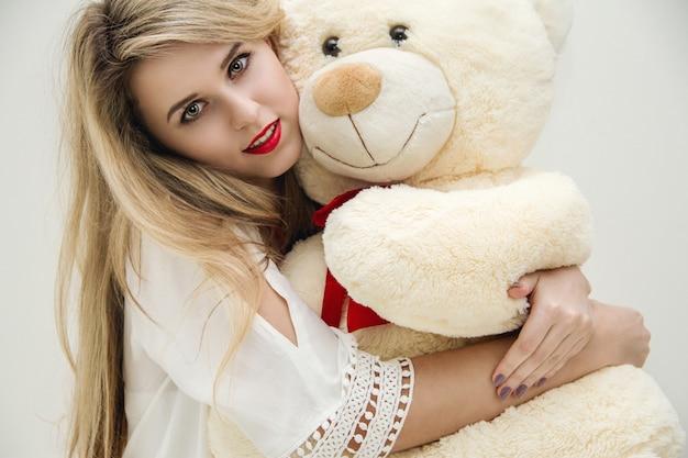 Blond meisje op haar bed en knuffelen een teddybeer