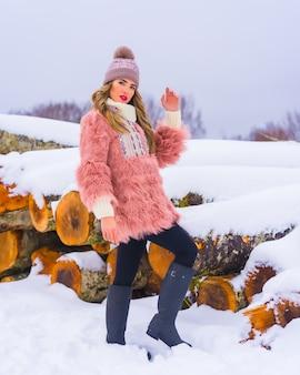 Blond meisje poseren in een roze bontjas en een paarse hoed in de sneeuw. naast enkele bomen die met ijs zijn gekapt, winterlevensstijl