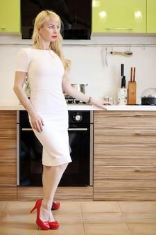 Blond meisje poseren op camera staande in de keuken naast kasten