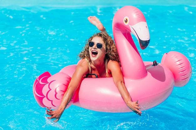 Blond meisje rust in het zomerbad op een opblaasbare roze flamingo in een badpak.