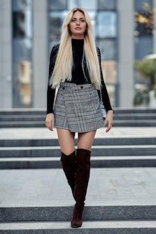 Blond meisje schoonheid wandelen in de straat in stijl kleding