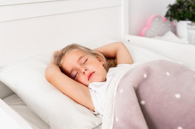 Blond meisje slapen op witte bed in lichte kamer thuis.