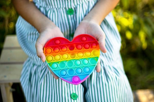 Blond meisje speelt met kleurrijke pop it. grappige trendy siliconen anti-stress kleurrijke sensorische duwspeelgoed popit en eenvoudig kuiltje. fladderend friemelen. regenboogkleurig hart, helpt bij autisme en stressverlichter.