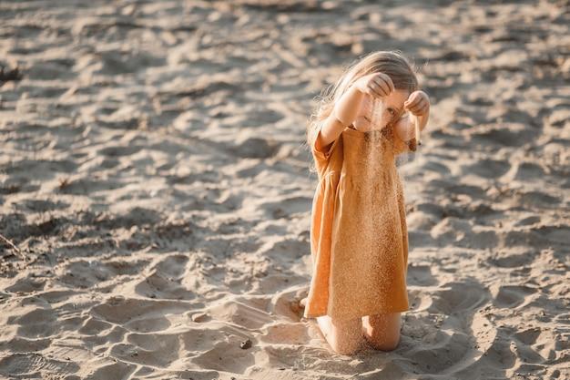 Blond meisje speelt op de rivier in het zand tegen de avondrood