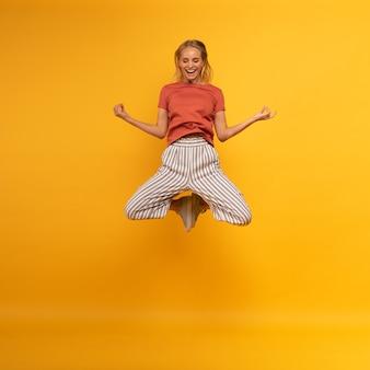 Blond meisje springt in yogas positie