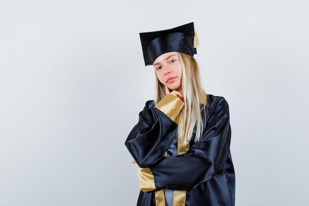 Blond meisje staat in denkende pose in afstudeerjurk en pet en kijkt peinzend