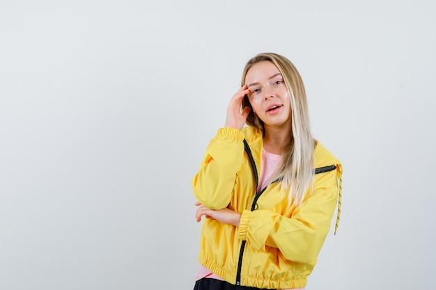 Blond meisje staat in denkende pose in gele jas en ziet er mooi uit