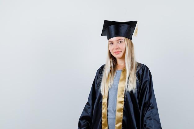 Blond meisje staat rechtop en poseert voor de camera in afstudeerjurk en pet en ziet er gelukkig uit.