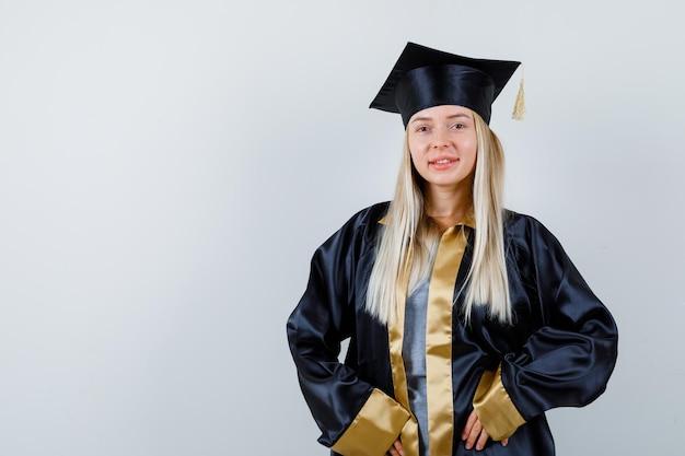 Blond meisje staat rechtop, glimlacht en poseert voor de camera in afstudeerjurk en pet en ziet er schattig uit.