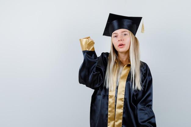 Blond meisje steekt één hand op in afstudeerjurk en pet en ziet er schattig uit