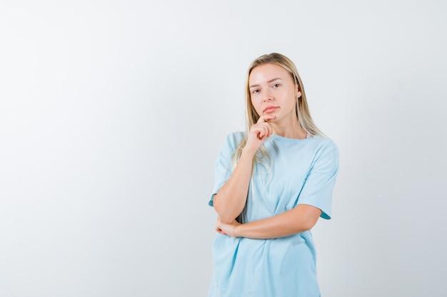Blond meisje steunt kin bij de hand, staande in denken pose in blauw t-shirt en peinzend, vooraanzicht op zoek.