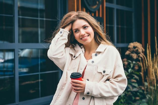 Blond meisje student meisje glimlacht en loopt rond de stad en staat