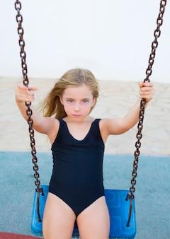 Blond meisje swingend op blauwe schommel met zwempak