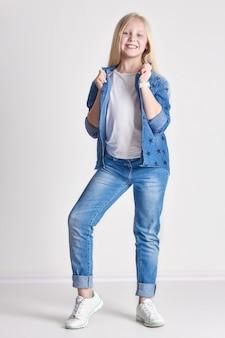 Blond meisje tiener in een denim kostuum, leuke kind mode kunst poseren. model poseren in de studio, zomerlook, schone huid