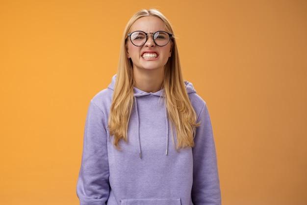 Blond meisje toon tanden waarschuwen kan zichzelf bijten, dwaas rond grimassen grappig dragen paarse hoodie bril staande oranje achtergrond beter niet rotzooien met mij, pranking vriend veel plezier.