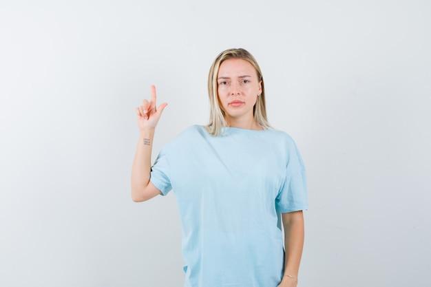 Blond meisje toont een minuut gebaar in blauw t-shirt en kijkt serieus, vooraanzicht.