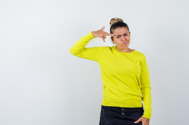 Blond meisje toont een pistoolgebaar bij het hoofd, trekt een grimas in een gele trui en zwarte broek en ziet er geïrriteerd uit