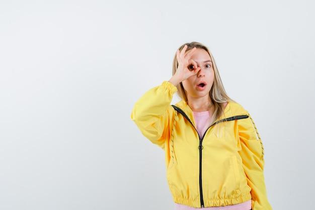 Blond meisje toont goed teken op oog in roze t-shirt en gele jas en kijkt verrast