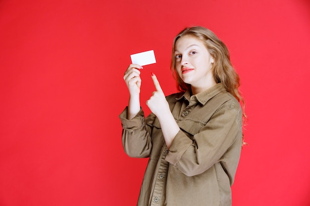 Blond meisje toont haar visitekaartje en voorzien van een netwerk.