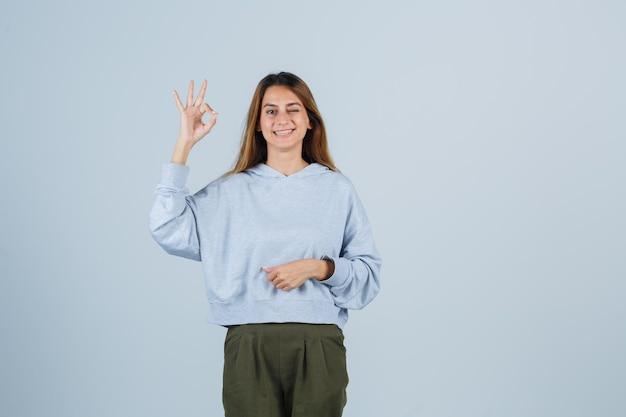 Blond meisje toont ok teken in olijfgroen blauw sweatshirt en broek en ziet er stralend uit, vooraanzicht.