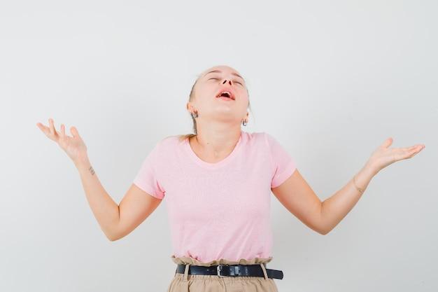 Blond meisje verhogen handen, hoofd terug buigen in t-shirt, broek en vredig, vooraanzicht.