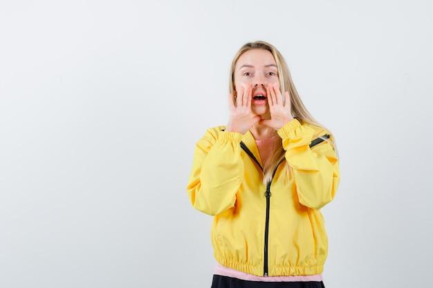 Blond meisje vertelt geheim met handen in de buurt van mond in gele jas en ziet er schattig uit