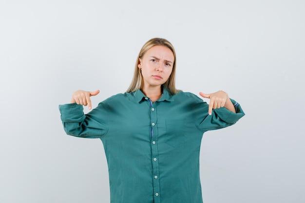 Blond meisje wijst naar beneden met wijsvingers in groene blouse en kijkt geïrriteerd