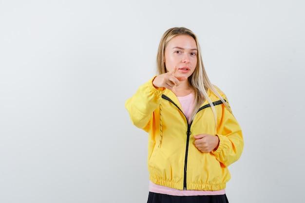 Blond meisje wijst naar de camera met wijsvinger, balde vuist in roze t-shirt en gele jas en ziet er serieus uit.