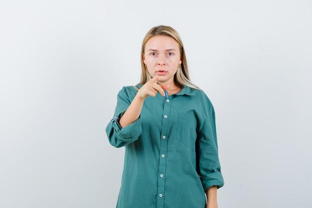 Blond meisje wijst naar de camera met wijsvinger in groene blouse en ziet er betoverend uit