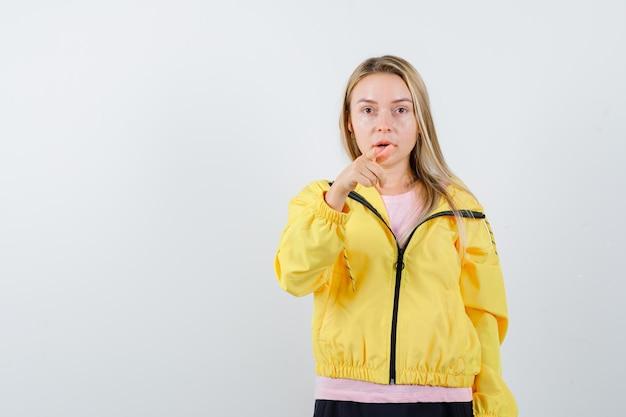 Blond meisje wijst naar de camera met wijsvinger in roze t-shirt en gele jas en ziet er serieus uit