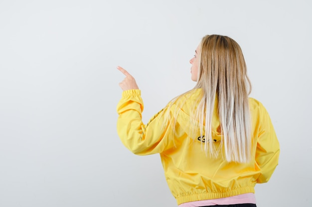 Blond meisje wijst naar links met wijsvinger, keert terug in roze t-shirt en gele jas en ziet er aantrekkelijk uit