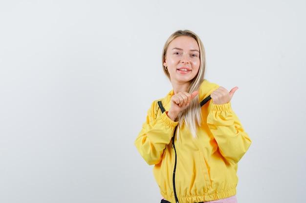 Blond meisje wijst opzij met duimen in t-shirt, jas en ziet er vrolijk uit