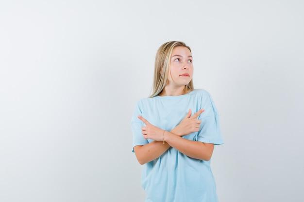 Blond meisje wijst tegengestelde richtingen, lippen bijten in blauw t-shirt en ziet er mooi uit. vooraanzicht.