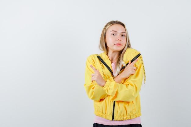 Blond meisje wijst tegengestelde richtingen met wijsvingers in roze t-shirt en gele jas en ziet er gelukkig uit