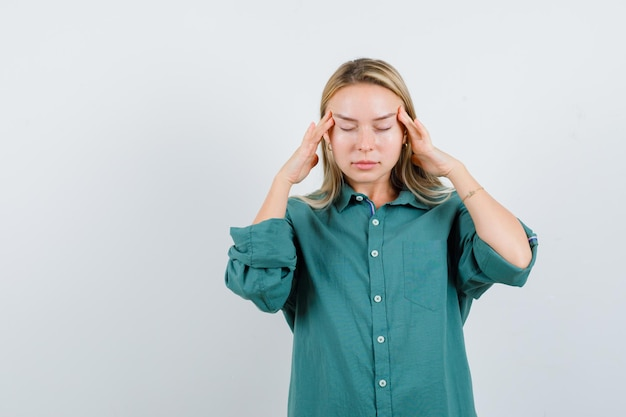 Blond meisje wrijft over haar slapen in een groene blouse en ziet er moe uit.