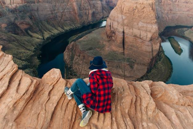 Blond meisje zit horseshoe bend in glen canyon national recreation area in de vroege dageraad
