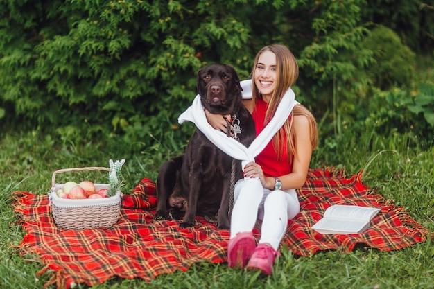 Blond meisje zit op het dekentapijt in het park met haar bruine hond