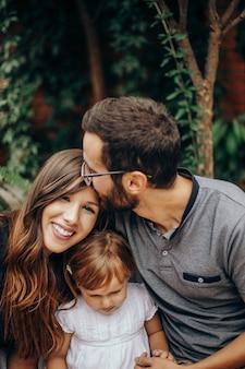 Blond meisje zit tussen ma en papa. vader kust moeder op het hoofd. dochter genieten met haar jonge ouders in de tuin. liefde en familie concept.