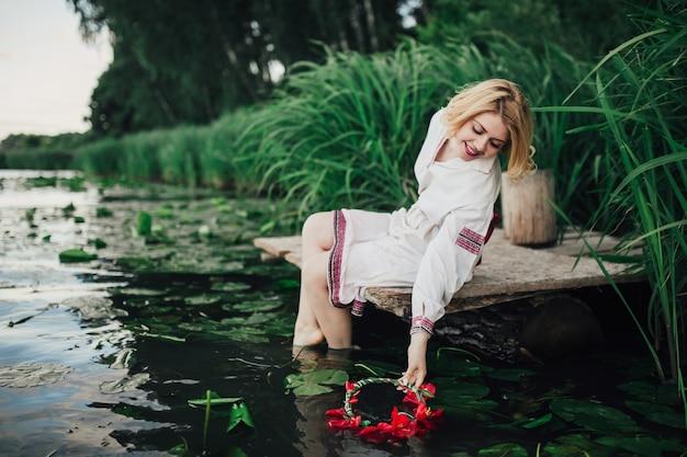 Blond meisje, zittend aan het water in het bos