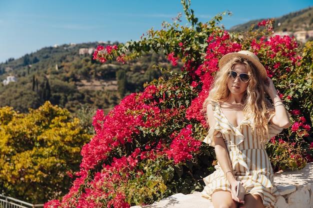 Blond meisje zittend op de weg grens met een prachtig uitzicht achter