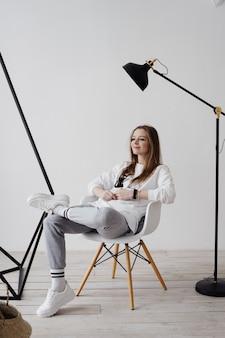 Blond meisje zittend op een fauteuil thuis in de werksfeer, werken vanuit huis, de vreugde van thuis zijn