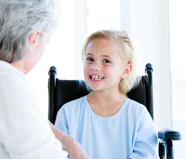 Blond meisje, zittend op een rolstoel te praten met haar grootmoeder